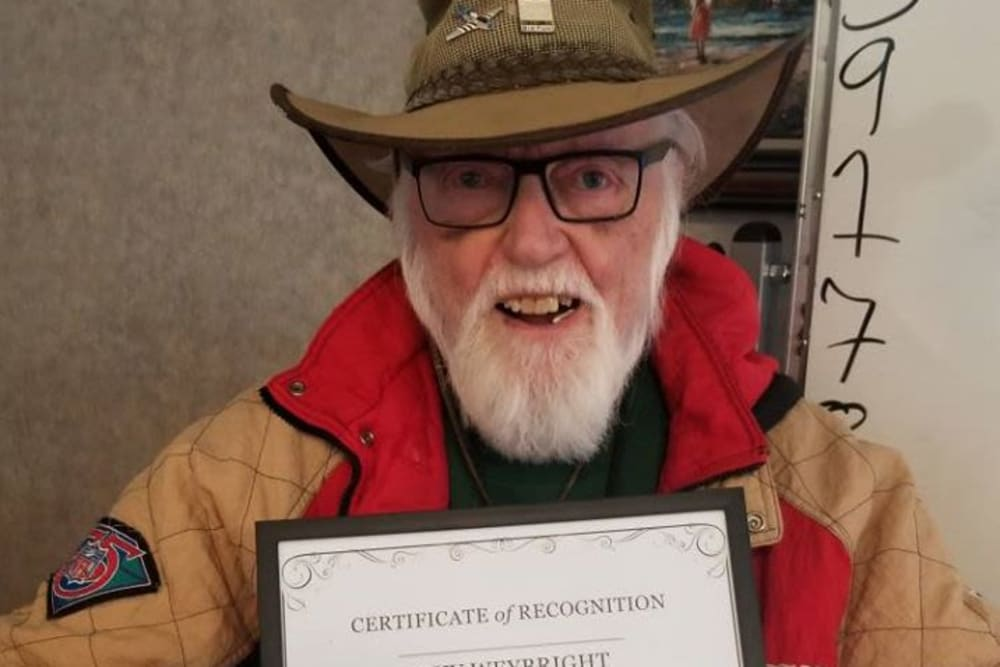 A resident holding up a certificate at Legacy Oaks of Sacramento in Sacramento, California