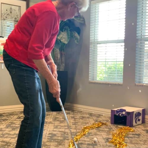 A resident playing indoor minigolf at Oxford Villa Active Senior Apartments in Wichita, Kansas