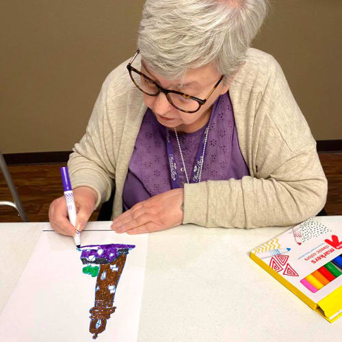 A happy resident painting at FountainBrook in Midwest City, Oklahoma
