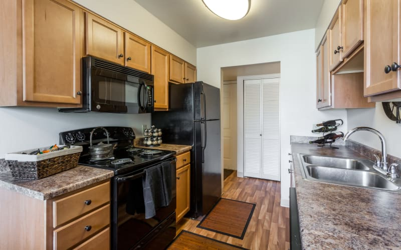 Oak cabinetry and black appliances in a kitchen at Royal Ridge Apartments in Midvale, Utah