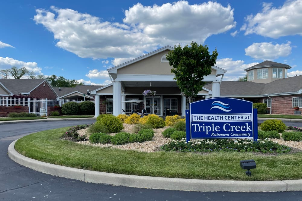 Sign and garden with building exterior of Triple Creek Retirement Community in Cincinnati, Ohio