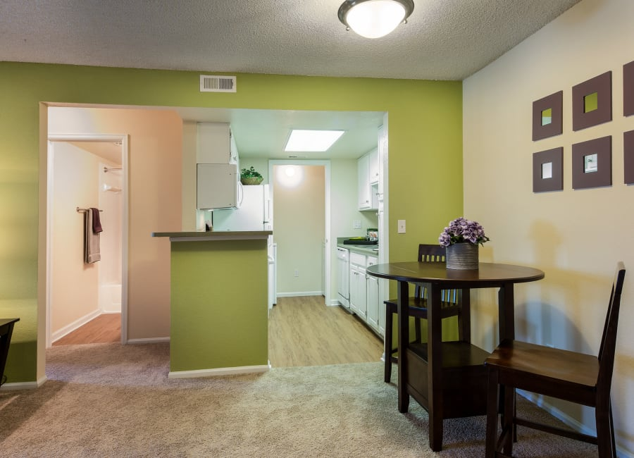 View of the modern kitchen from the dining area of a model home at Waterfield Court Apartment Homes in Aurora, Colorado