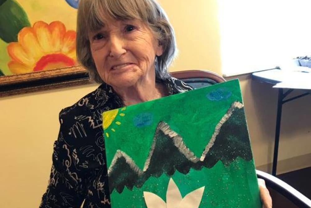 A resident holding her painting at The Willows at Howell in Howell, Michigan