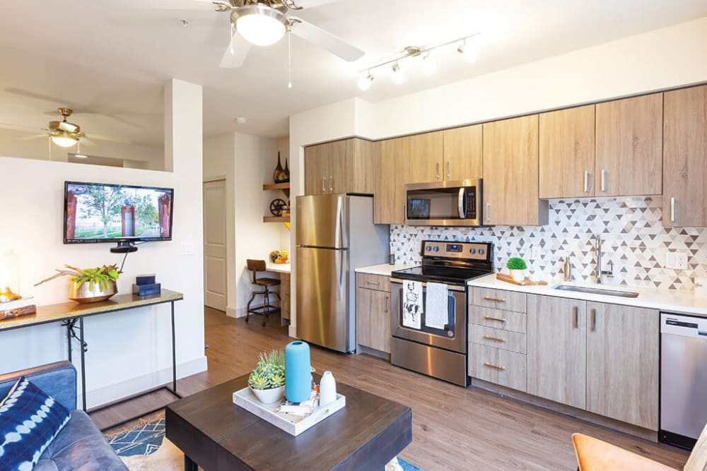 Custom cabinetry and a ceiling fan in a model home's open-concept kitchen and living areas at ArLo Apartments in Portland, Oregon