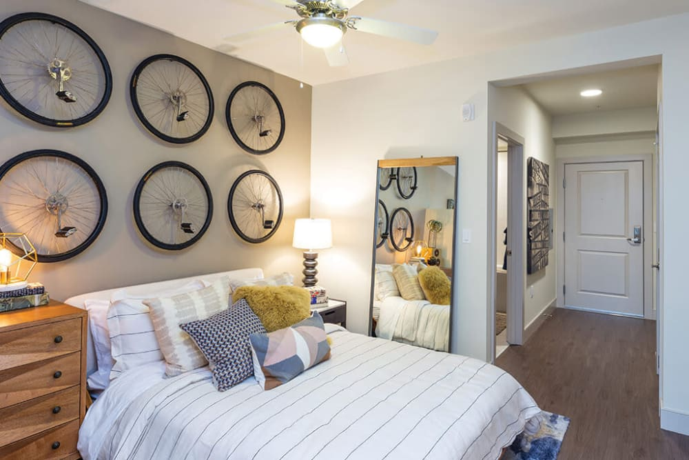 Well-furnished primary bedroom with a ceiling fan in a model home at ArLo Apartments in Portland, Oregon