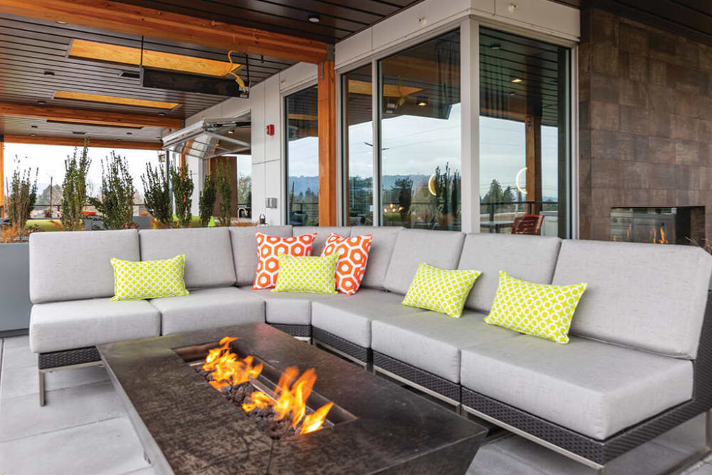 Fire pit surrounded by comfortable seating at the rooftop lounge at ArLo Apartments in Portland, Oregon