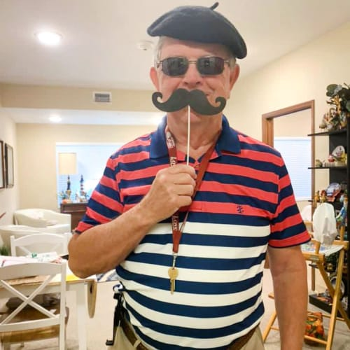 Resident in a beret holding a funny mustache up to their face at The Oxford Grand Assisted Living & Memory Care in McKinney, Texas