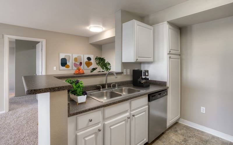 Renovated kitchen with white cabinets at Pebble Cove Apartments in Renton, Washington