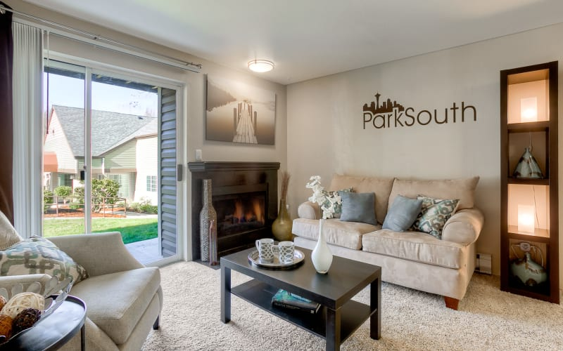 Cozy living room with a fireplace at Park South Apartments in Seattle, Washington