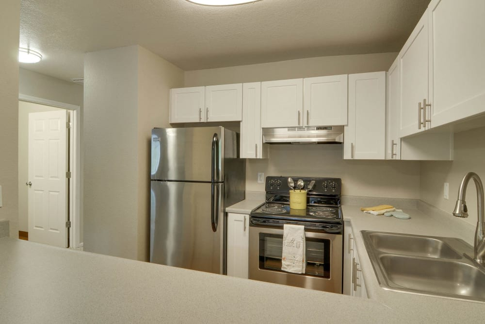 Kitchen with stainless steel appliances and white cabinets at Carriage House Apartments in Vancouver, Washington