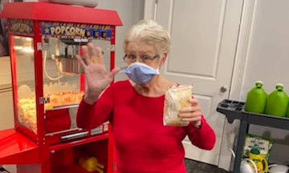 Resident grabbing popcorn at The Mansions at Gwinnett Park Assisted Living and Memory Care in Lawrenceville, Georgia