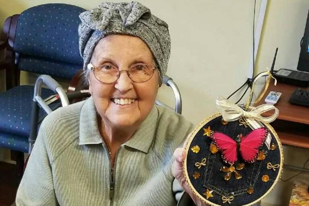 A resident holding up her art at Westlake Health Campus in Commerce Township, Michigan