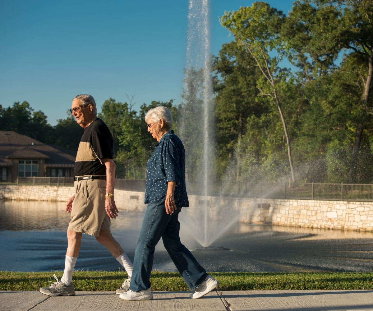 Two residents walking in front of the fountain at Watercrest at Kingwood in Kingwood, Texas
