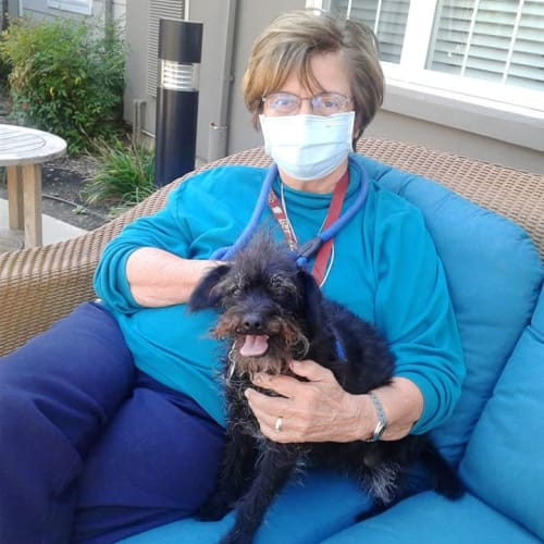 Resident seated outside beside her small black dog at The Oxford Grand Assisted Living & Memory Care in McKinney, Texas