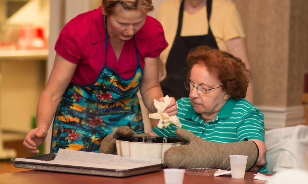 Resident cooking with help from a caretaker at Governor's Village in Mayfield Village, Ohio