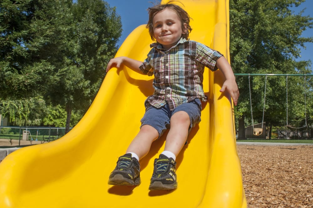 Child going down the slide in the playground at Oak Meadow Apartments in Chico, California