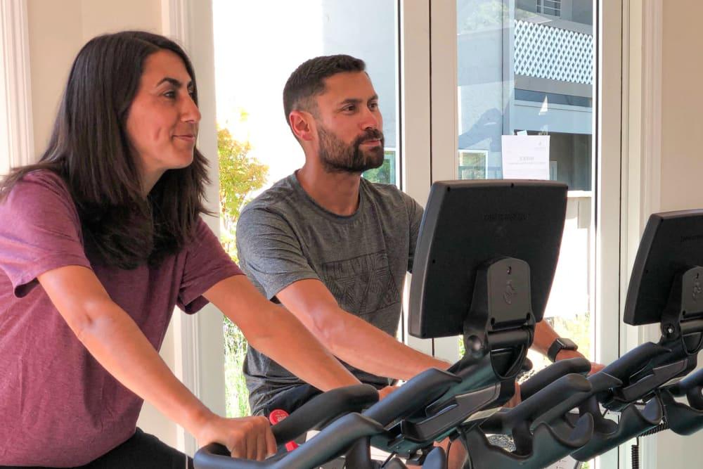 Resident using the fitness center at Halford Gardens Apartments in Santa Clara, California