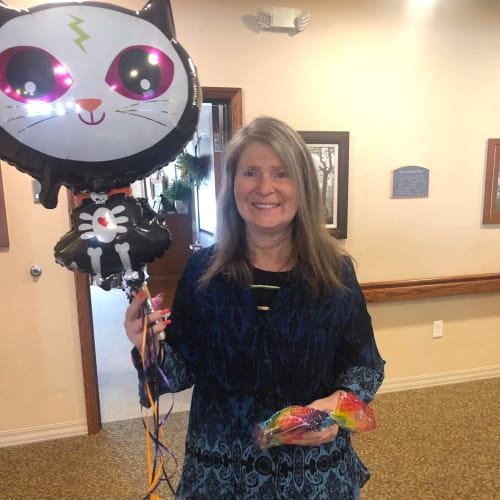 Resident holding a cat balloon and a goodie bag at Oxford Glen Memory Care at Carrollton in Carrollton, Texas