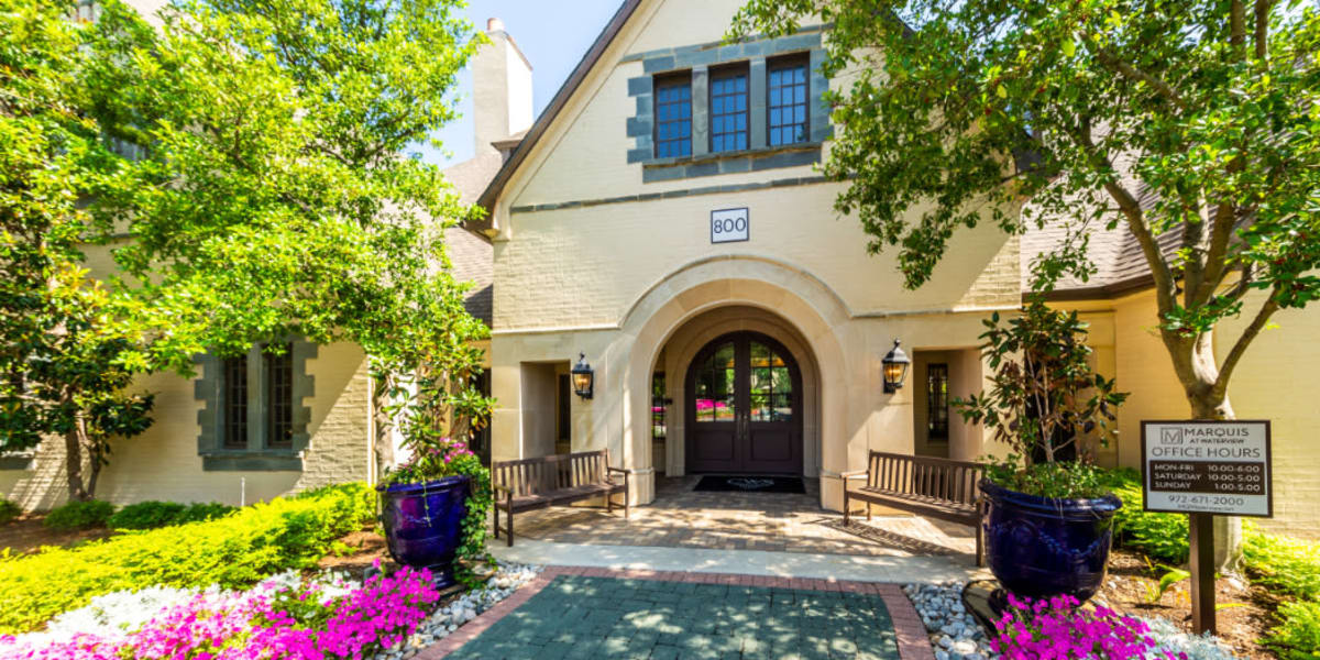 Leasing office main entrance with paved path and flowers along sides at Marquis at Waterview in Richardson, Texas