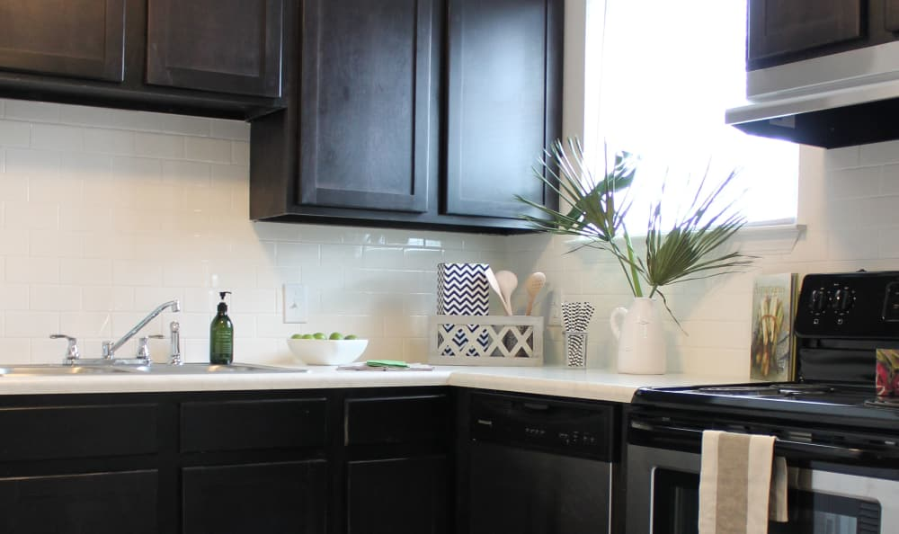 Showcasing dark wood cabinetry, stainless-steel oven, and tile backsplash in model kitchen at Palmilla Apartments