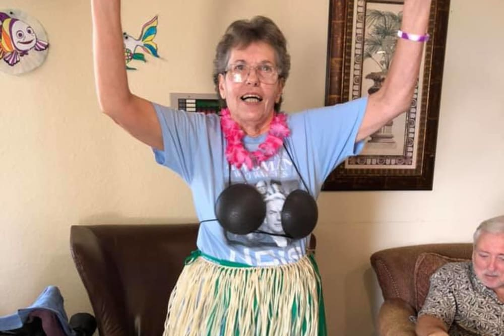 A resident dressed in a grass skirt at Balmoral Assisted Living in Lake Placid, Florida