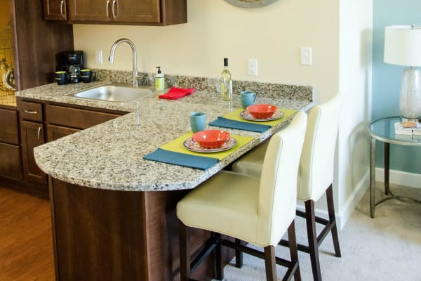 Kitchenette with granite counter tops and island seating at First & Main of Auburn Hills in Auburn Hills, Michigan