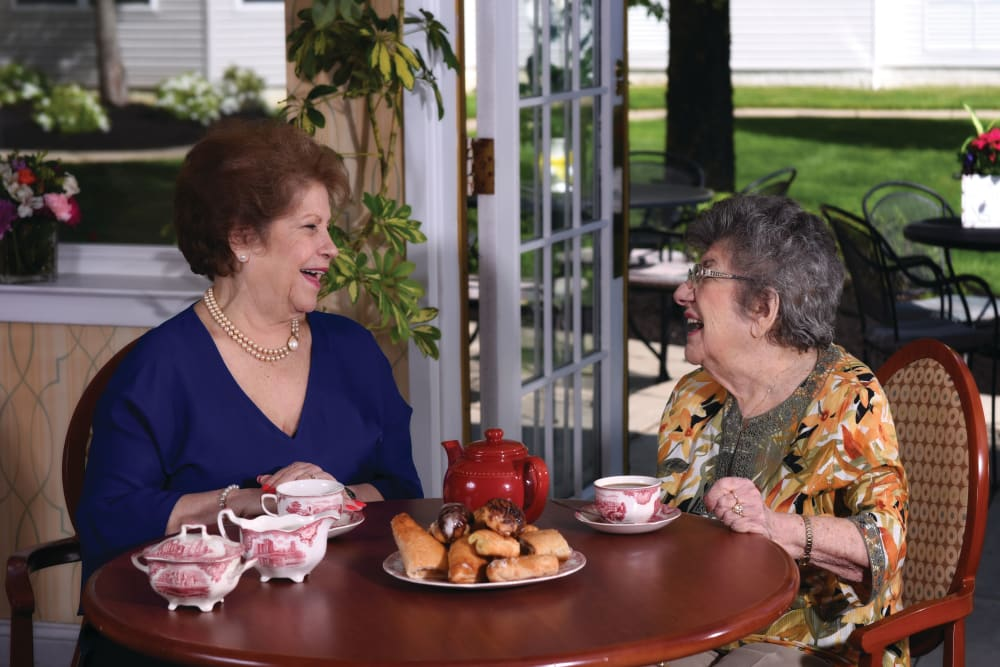 Senior women laughing over tea at Symphony at Delray Beach in Delray Beach, Florida