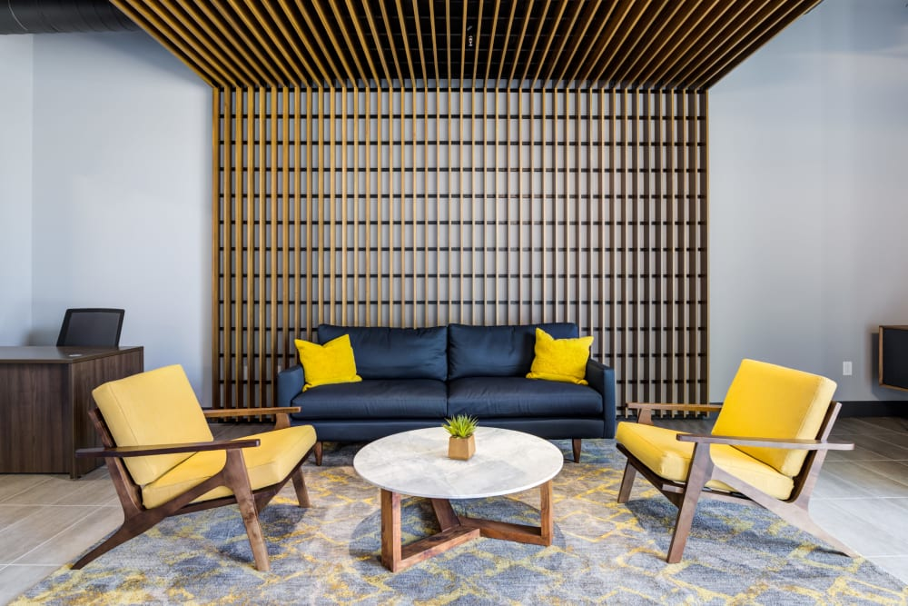 Resident lounge with coffee table and yellow accent chairs at Lumen Apartments in Everett, Washington