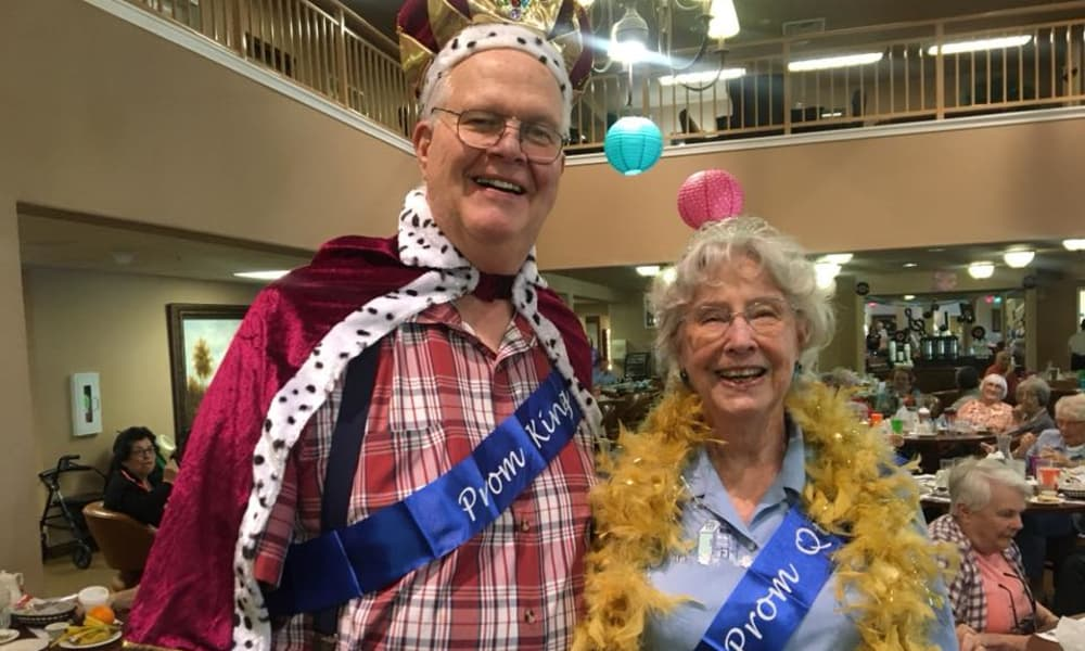 Prom king and queen posing for a photo at Sanford Estates Gracious Retirement Living in Roswell, Georgia
