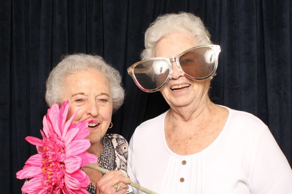 Two resident friends enjoying a party at Merrill Gardens at Willow Glen in San Jose, California.