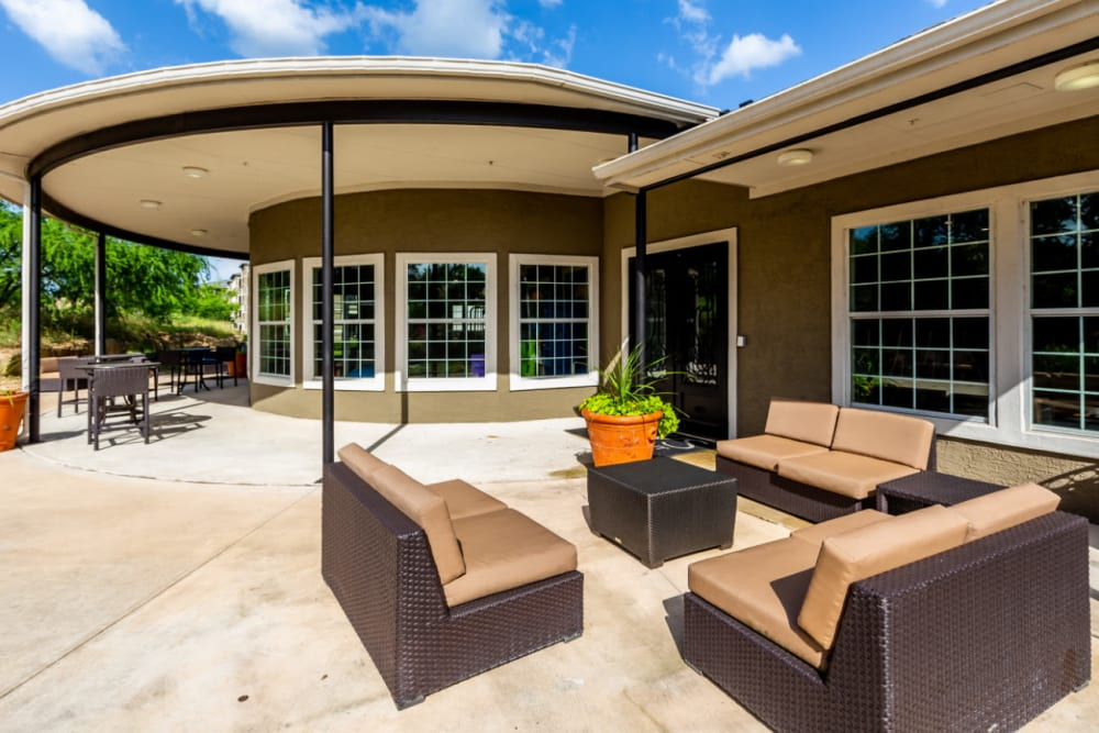 Sitting area with cushioned chairs and tall chairs with tables outside community clubhouse at Marquis at Stone Oak in San Antonio, Texas