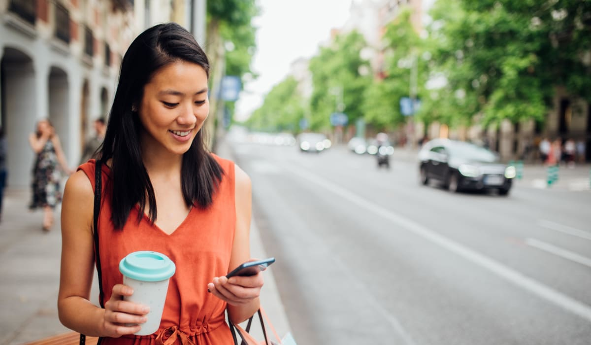 Resident checking her phone while walking to work with her morning coffee downtown near Rancho Los Feliz in Los Angeles, California