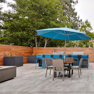 Table with an umbrella and chairs at the main outdoor common area at Mia in Palo Alto, California