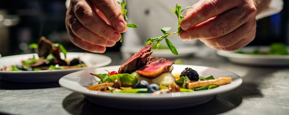 Chef putting the garnish on a complete dish at The Springs at Lake Oswego in Lake Oswego, Oregon