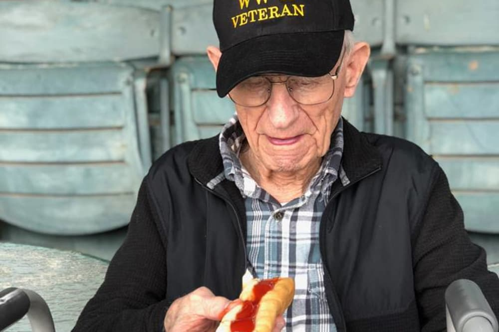 A veteran resident eating a hot dog at North River Health Campus in Evansville, Indiana