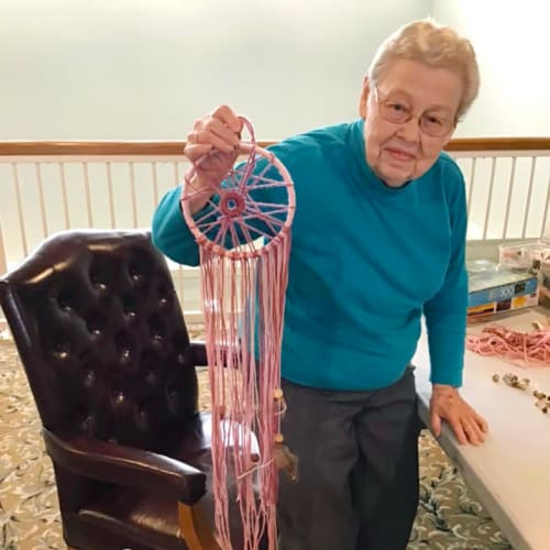 A happy resident holding up a pink dreamcatcher at Canoe Brook Assisted Living & Memory Care in Catoosa, Oklahoma