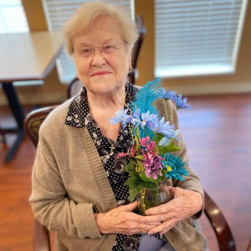 Seated resident holding flowers at Oxford Glen Memory Care at Owasso in Owasso, Oklahoma