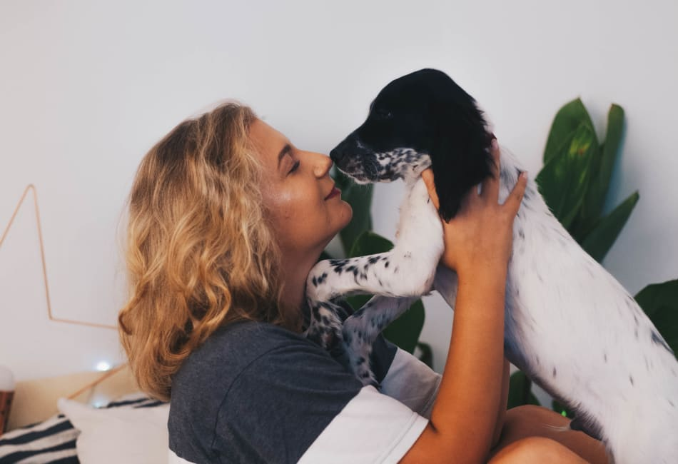 Resident giving her dog a kiss in their new home at Terra Martinez in Martinez, California