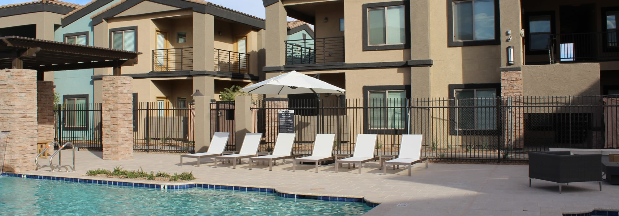 Luxury pool with poolside lounge chairs at The Maxx 159 in Goodyear, Arizona