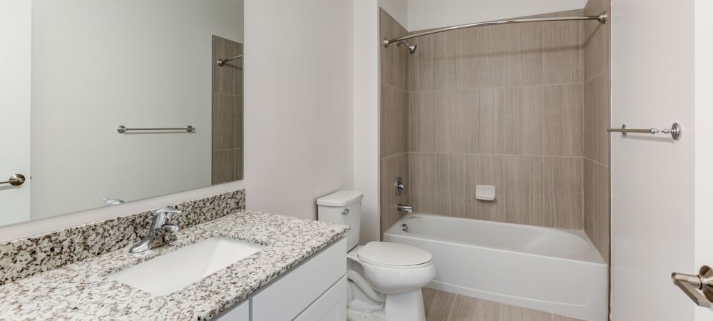 Spacious bathroom with large mirror and ample counter space at Main Street Apartments in Rockville, Maryland