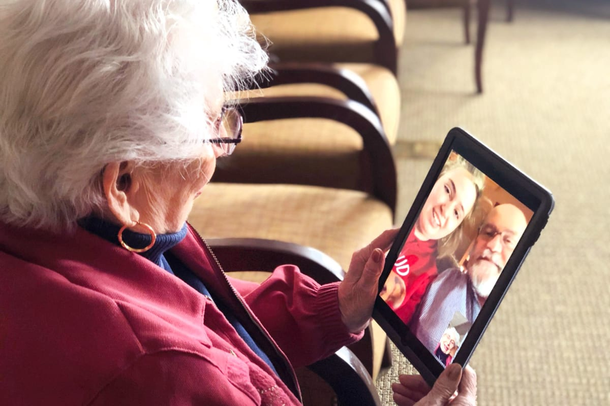 A resident using a tablet at Oxford Glen Memory Care at Carrollton in Carrollton, Texas