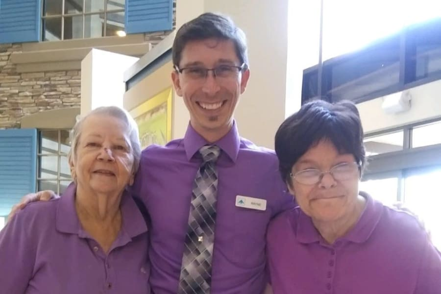Staff and residents posing in purple attire at Bella Vista Senior Living in Mesa, Arizona