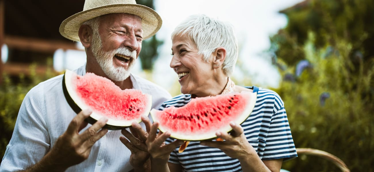 Residents embrace enjoying sliced watermelon at a Truewood by Merrill location