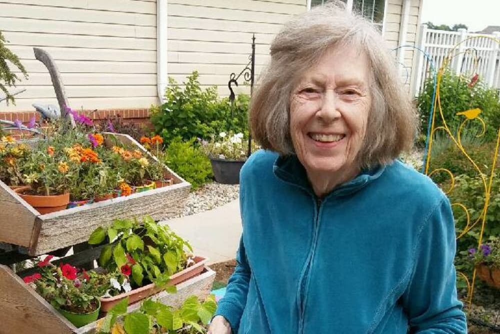 A happy resident in the community garden at Bethany Pointe Health Campus in Anderson, Indiana