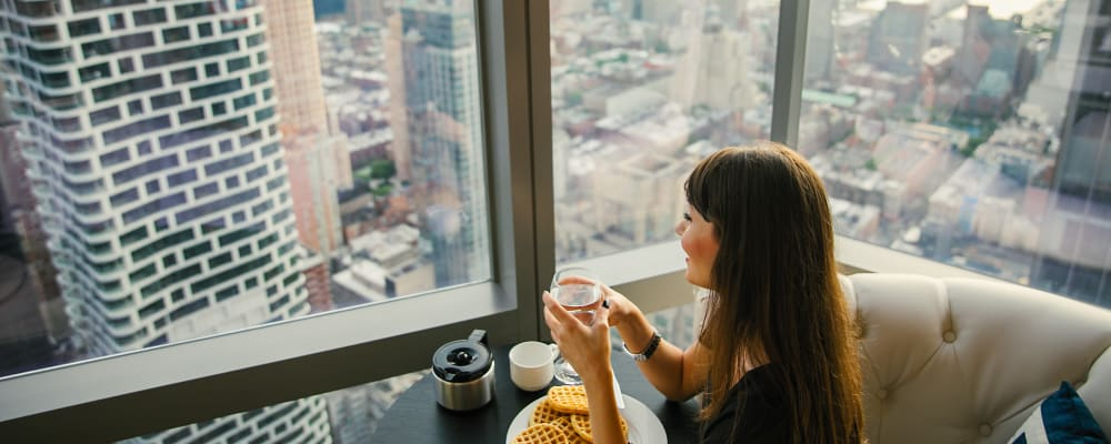 Women enjoying the amazing city view from her living room at The Larstrand in New York, New York