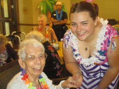 Happy volunteer with senior enjoying activities at Eastern Star Masonic Retirement Campus in Denver, CO