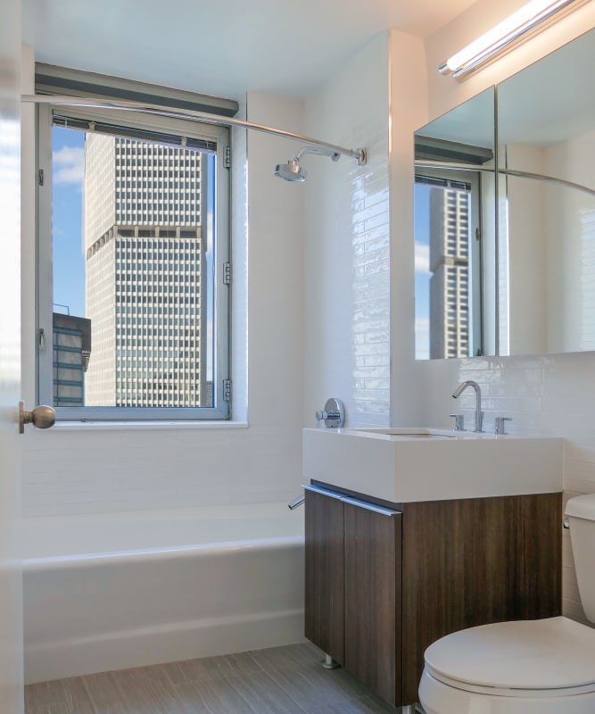 A modern bathroom with a large vanity mirror at The Metropolis in New York, New York
