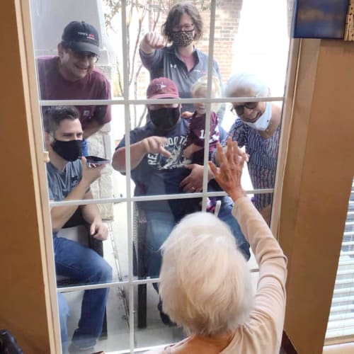 A resident interacting with her family through a window at Oxford Glen Memory Care at Grand Prairie in Grand Prairie, Texas