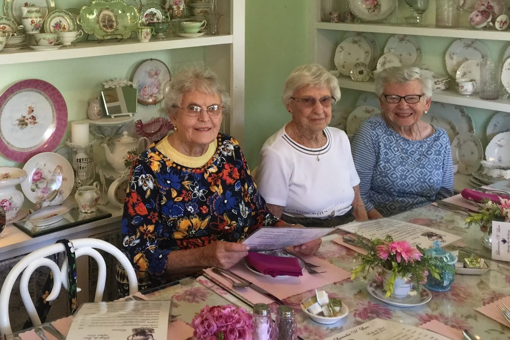 Resident friends about to join a meal at Merrill Gardens at Solivita Marketplace in Kissimmee, Florida.