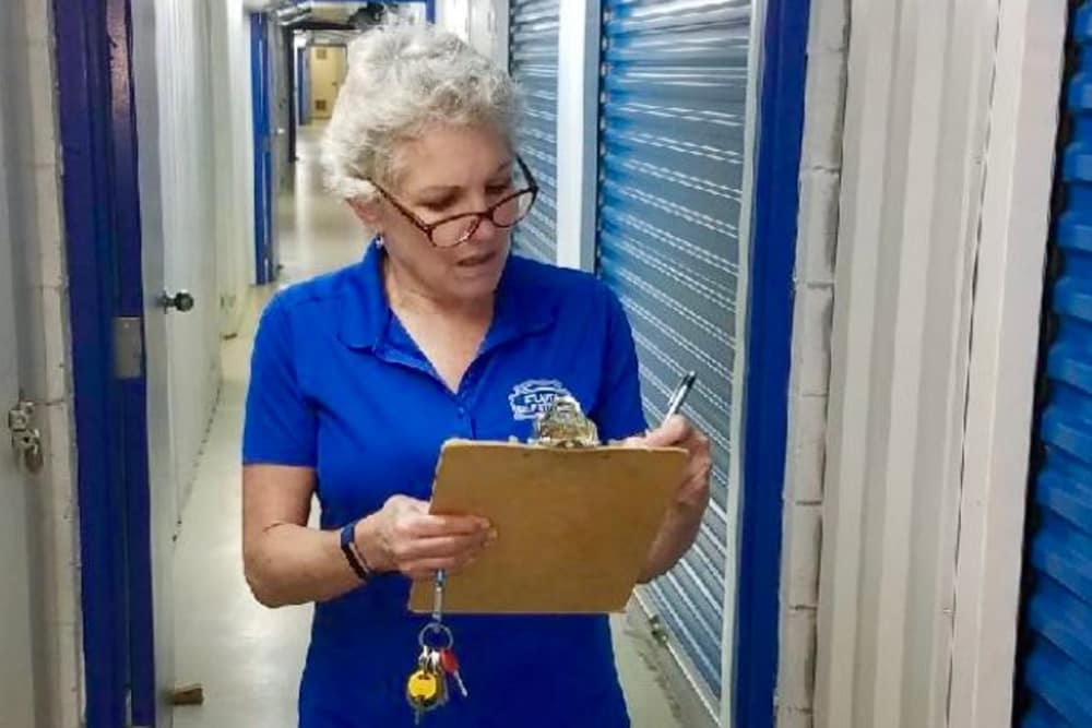 woman writing on clipboard in storage facility